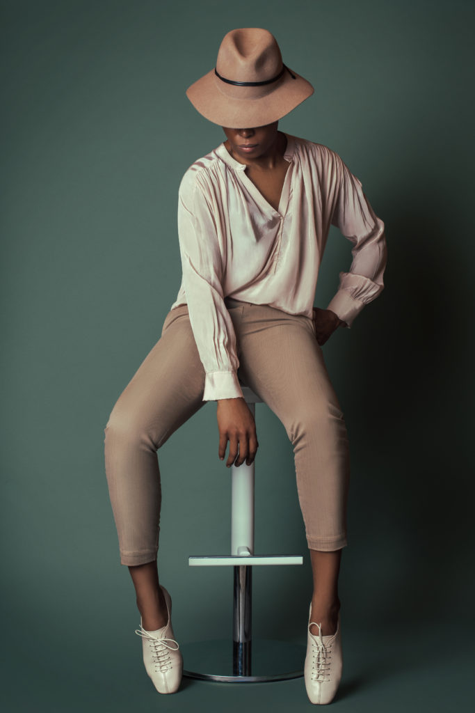 Black woman sitting on white bar chair for shoe trends spring 2021