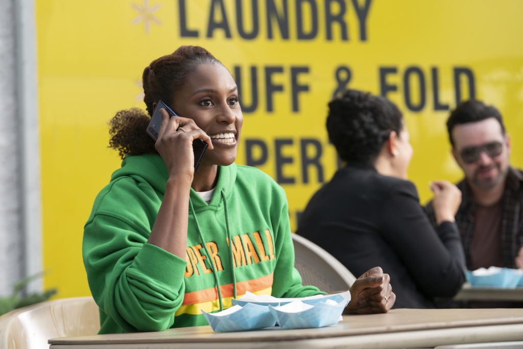 Issa Rae on the phone while eating during the show INSECURE