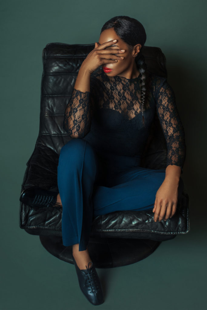 Black woman sitting on black leather chair for shoe trends spring 2021