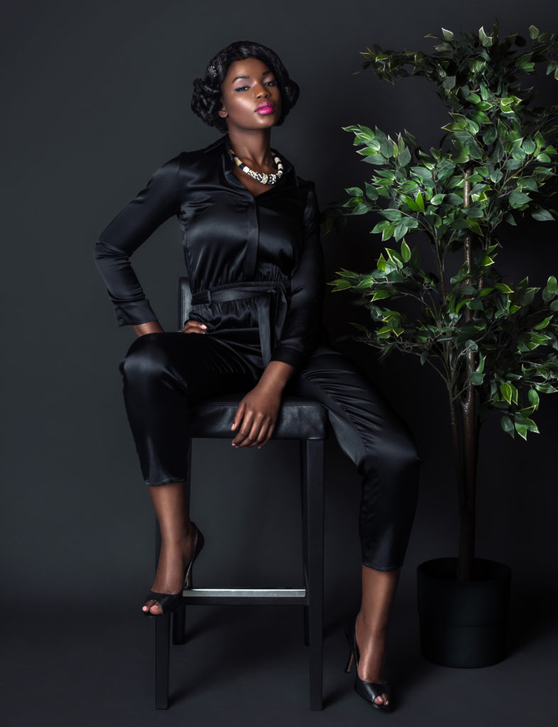 Black girl sitting on a bar chair wearing a black Silk Dress for Spring 2021 Fashion Trends