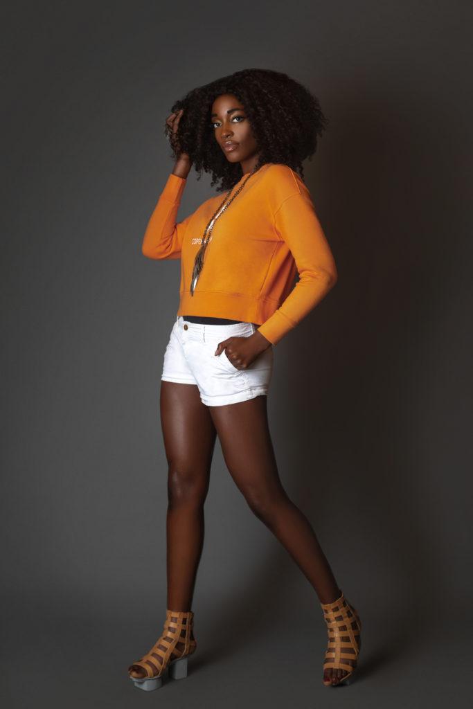 Black girl wearing an orange sweatshirt for Spring 2021 Fashion Trends