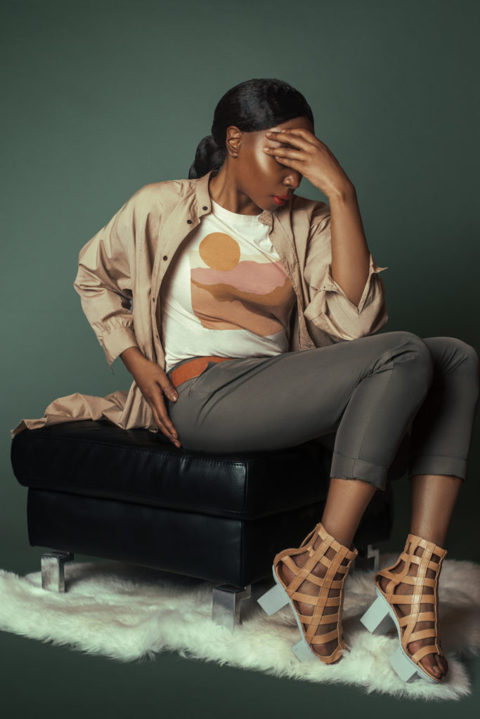 Black girl wearing a beige shirt with grey pants for Spring 2021 Fashion Trends