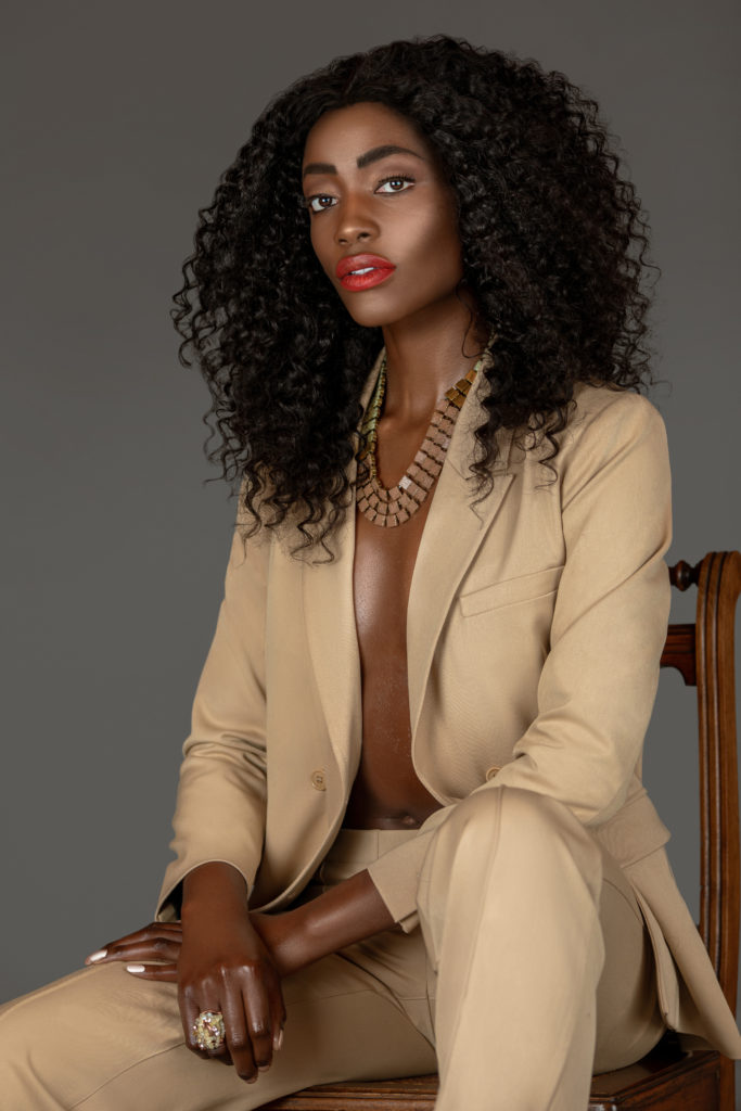 Black model in beige suit sitting on a wooden chair