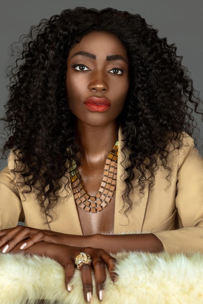 Black model in beige suit sitting