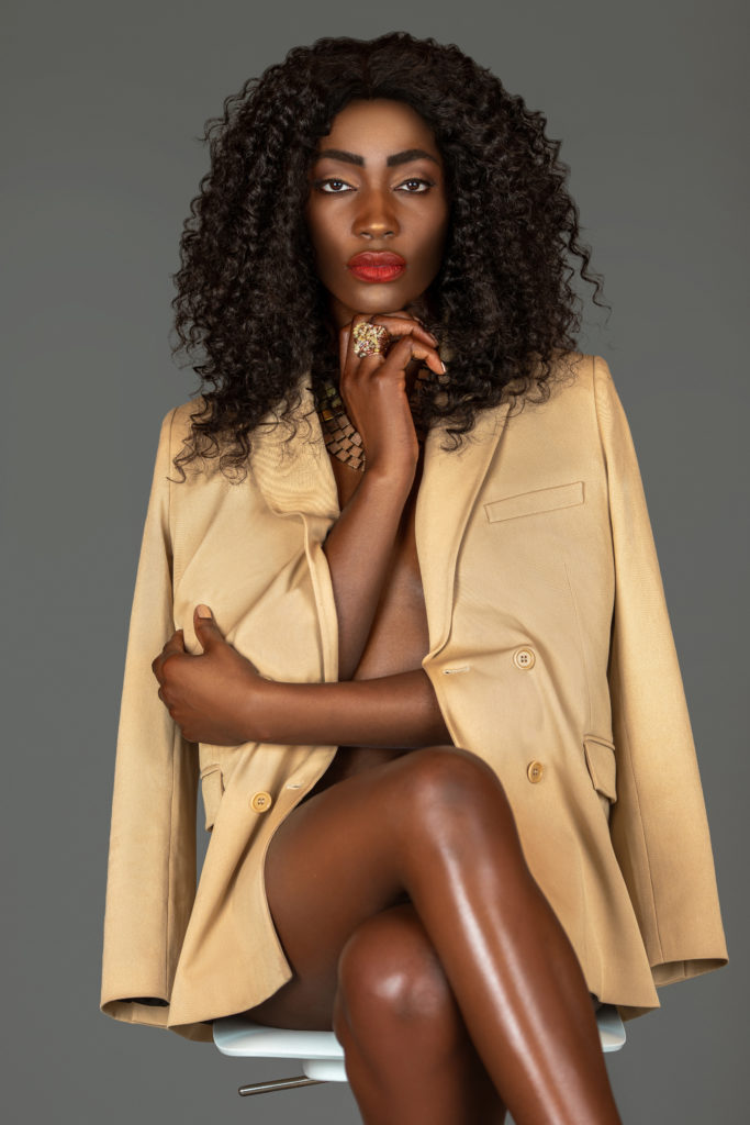 Contact an agency: Black model in beige suit sitting on a bar chair