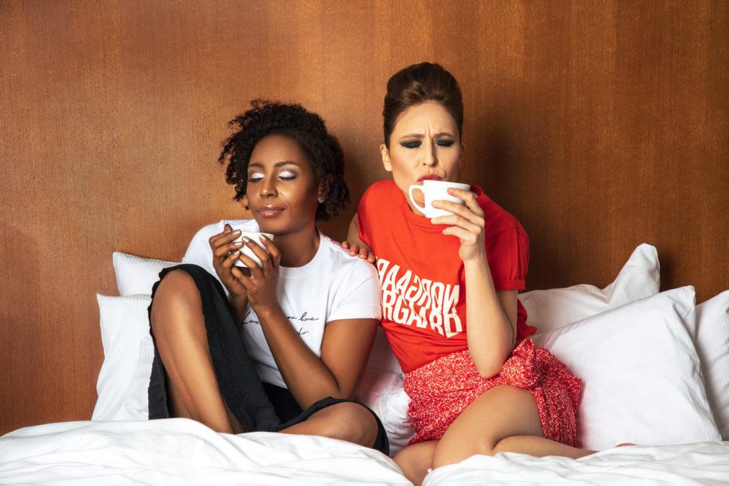 Britta Steffenhagen and Sophia Lenore on bed drinking coffee